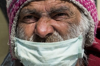 Bezdomovec s ochranným rúškom na tvári na Námestí SNP v Bratislave.