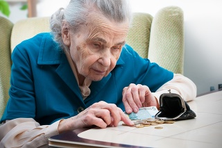 elderly caucasian woman counting coins in her hands