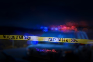 A stock photo of a Police Line 'Do Not Cross' caution tape with a defocused police car with sirens flashing red and blue.