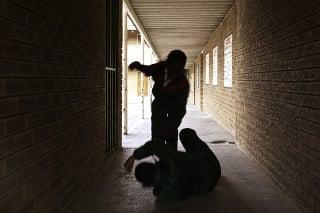 Two school kids fight in a dark passageway of their school, almost silhouette.