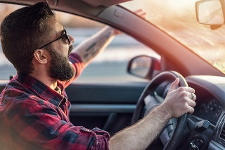 Angry young man gesturing and shouting at other drivers on the road