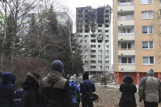 Na snímke ľudia sa pozerajú na zhorený bytový dom v Prešove.