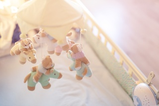 Close-up baby crib with musical animal mobile at nursery room. Hanged developing toy with plush fluffy animals. Happy parenting and childhood, expectation delivery of a child concept.