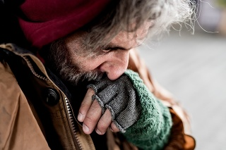 A close-up view of homeless beggar man standing outdoors in city, rubbing nose.