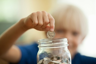 Little boy saving coin in a money jar