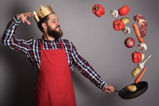 Cooking man concept, king of kitchen,bearded man in checked shirt, drop up meat and vegetables from a pan, studio shot on gray background