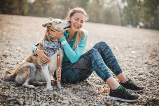 Adult woman in sports clothing spend time on beach of the lake with her dog