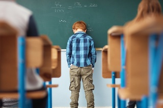 Rear view shot of an elementary school boy leaning with his head on the chalkboard in class