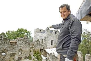 Mojmír Choma ukazuje miesto, kde z kopy kamenia vyrástla budova so strechou.