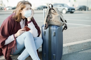 Young woman wearing medical mask, with a suitcase
