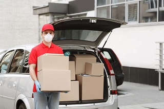 Delivery of big parcels by car with courier at home concept. Curier in medical mask and gloves holds cardboard boxes near front door