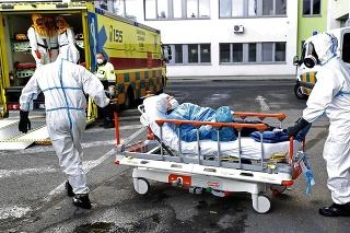 Záchranári v špeciálnych ochranných odevoch pomáhajú pri prevoze pacienta s ochorením COVID-19.
