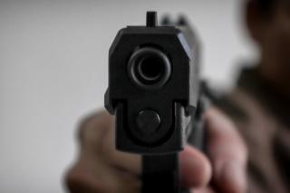 Gunman aiming his target.terrorism shoots a pistrol handgun.Criminal murder and violent concept - Film grain effect