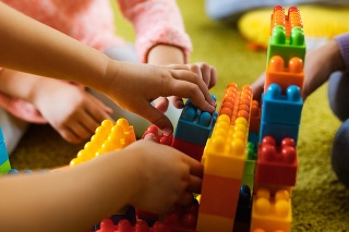 Close up of two unrecognizable kids building something with plastic blocks on carpet at playroom.