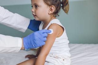 Nurse vaccinating a young Caucasian girl.