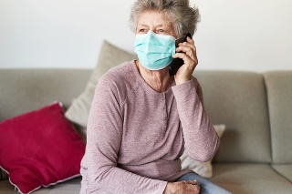 A senior citizen sits alone on her sofa in the living room wearing a respirator or surgical mask and looks sadly and frightened out of the window and into the camera while on the phone