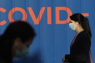 Žena s ochranným rúškom čaká v rade na odbererovom mieste na testovanie na ochorenie COVID-19 v Prahe.