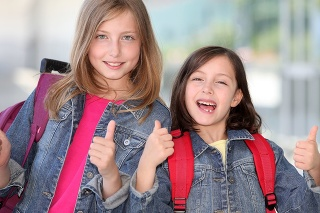Girls showing thumbs up in front of school building