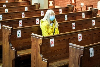 Color image depicting a senior woman in her 70s sitting alone in a church while wearing a protective face mask. The pews are mark with ticks and crosses to delineate a social distancing system during the covid-19 pandemic. Room for copy space.