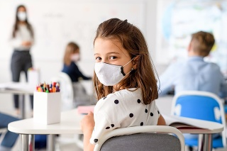 Child with face mask back at school after covid-19 quarantine and lockdown, looking at camera.