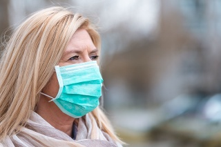 Portrait of an adult caucasian woman wearing a protective face mask outdoors.
