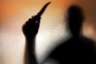 Colour backlit image of the silhouette of a man wielding a sharp knife in an aggressive way. The silhouette is distorted, and the arms elongated, giving an alien-like quality. The image is sinister and foreboding, with an element of horror. The image conveys a domestic violence, knife crime theme. Horizontal image with copy space.
