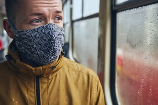Man wearing face mask in public transportation. Themes social distancing and personal protection.