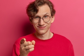 Photo of delighted mysterious male nerd points at camera with index finger and looks curiously, selects someone, wears spectacles and casual jumper, isolated on pink studio wall. Hmm, interesting