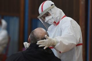 Zdravotníčka v ochrannom odeve odoberá vzorku počas testovania na COVID-19 v Trnave.