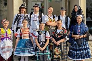Folkloristi pred prvou vlnou pandémie na schodoch do Domu Matice slovenskej a v ochranných odevoch.