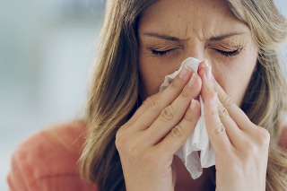 Shot of an attractive young woman feeling ill and blowing her nose with a tissue at home