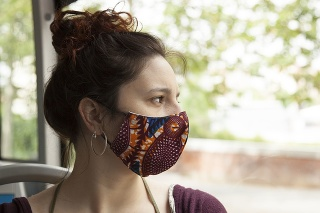 Spanish curly redheaded empowered woman wearing fabric handmade colorful cotton protective mask sitting on an empty bus looking through the window with negative space. Coronavirus mask wearing trends.