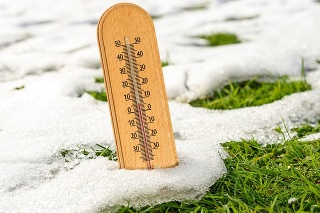 Spring time concept - mercury wooden thermometer in melting snow and growing green grass on a sunny day