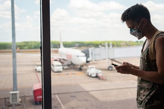 Young man with protective mask is using smart phone while waiting his flight at the airport.