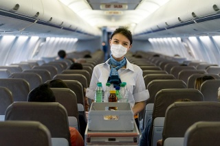 Portrait of a flight attendant serving food and drinks in an airplane wearing a facemask during the COVID-19 pandemic