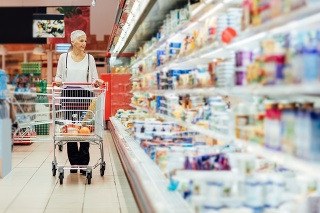 Mature smiling woman shopping in local supermarket. She is shopping groceries. Walking by refrigerator with dairy product and pushing shopping trolley.
