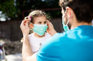 Single father applying pollution mask to his daughter. They are outside.