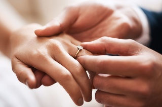 Cropped shot of an unrecognizable groom putting a diamond ring on his wife's finger during their wedding