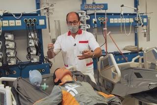 Anesteziológ Jakub Vallo ukazuje na umelej figuríne, ako prebieha intubácia pacienta na pľúcny ventilátor.