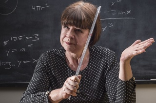 A grumpy older female teacher in front of the classroom