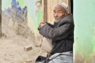 Hotan, China-October 4, 2017: Uyghurs are a Turkic people living mainly in the Xinjiang Uyghur Autonomous region. Old man in dusty clothes sits on the lintel of a door-street of the Livestock Market.