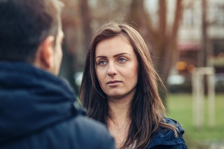 Couple arguing face to face outside in the park