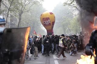 Demonštranti sledujú členov poriadkovej polície počas prvomájovej demonštrácie v Paríži.