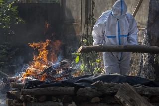 Rodinný príslušník pacienta, ktorý zomrel na COVID-19, robí pohrebný rituál v meste Guwahati v Indii.