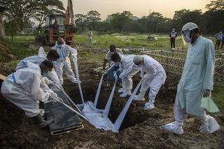 Príbuzní a mestskí zamestnanci odetí v špeciálnych ochranných odevoch pochovávajú do hrobu tele obete ochorenia COVID-19 v indickom meste Gauhátí