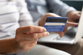 Close wife fingers holding plastic credit card on background computer on husband lap, old couple booking hotel using on-line app service and website, make online payment, shopping via internet concept