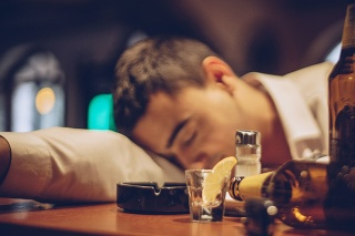 Young drunk man sleeping on bar counter in pub