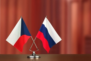 Two crossed national flags on wooden table