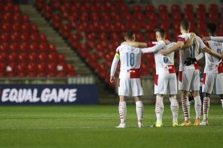 Brankár Arsenalu Londýn Alexandre Lacazette (vľavo) kľačí, futbalisti Slavie nie.