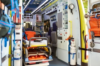 View from open rear doors of unoccupied ambulance interior with equipment required to stabilize an ill or injured person and transport them to hospital.